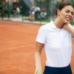 Fit woman tennis player with injury on a clay tennis court