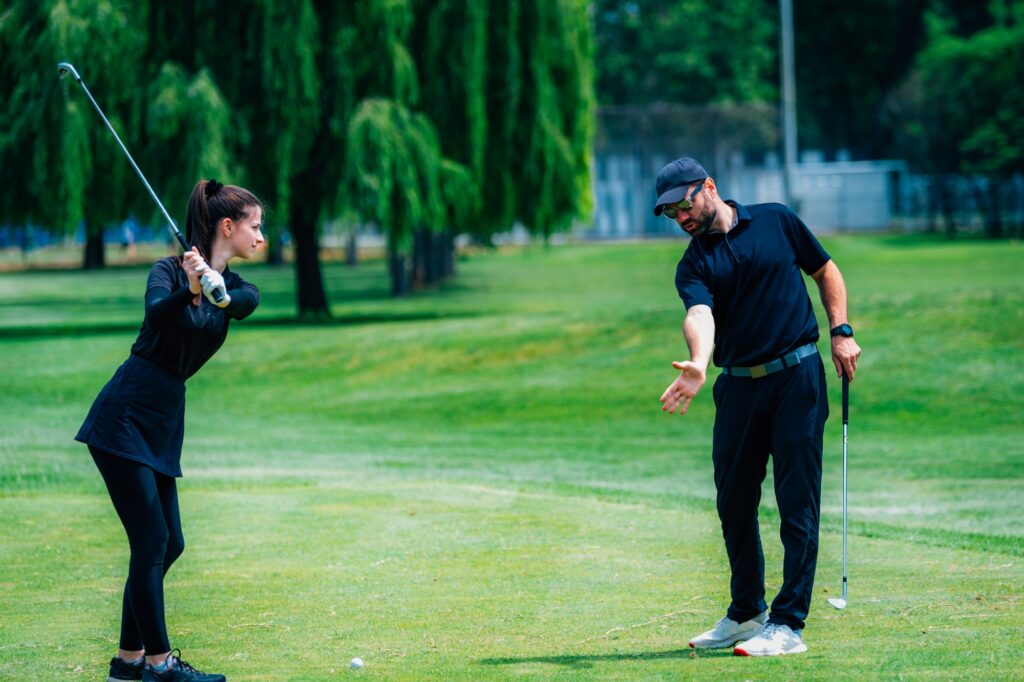 Playing golf. Young woman playing golf with golf instructor